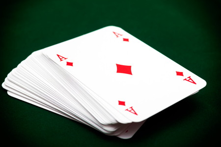 Deck of cards with ace of diamond on top. Green background