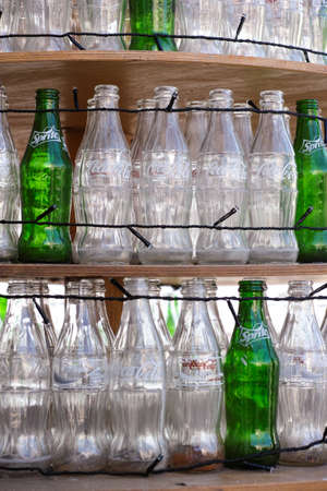 sprite: Paphos, Cyprus - December 11, 2015 Empty bottles of Coca-Cola and Sprite standing in a rows on wooden shelves with lights.