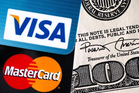 one hundred dollar bill: Tambov, Russian Federation - April 02, 2016 Visa and MasterCard logo on credit cards on one hundred dollar bill. Studio shot.