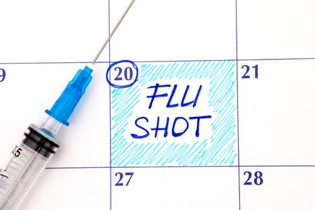 Reminder Flu Shot in calendar with syringe. Close up.