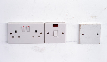 light switch: Power sockets and light switch on dirty white wall. Stock Photo