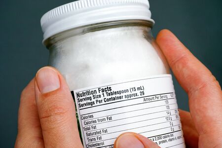 Jar of organic coconut oil with nutrition facts in woman hands. Closeup. Standard-Bild