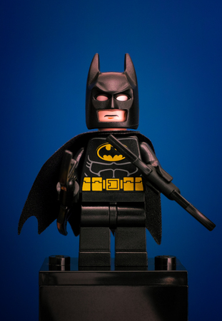 batman: Tambov, Russian Federation - June 08, 2015 Lego Batman minifigure with batarangs on blue background. Studio shot. Editorial