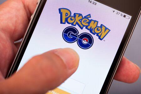 Tambov, Russian Federation - July 13, 2016 Person hand starting Pokemon Go application on apple iPhone5s. Studio shot.