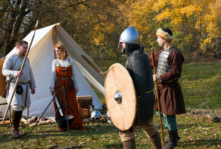 middleages: Tambov, Russian Federation - October 12, 2014 Reconstruction of old Russian medieval life. One woman with sword and three men with medieval weapons stay near  cast iron pot and white tent. Editorial