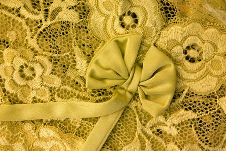 guipure: Yellow lace with bow background. Close up. Stock Photo