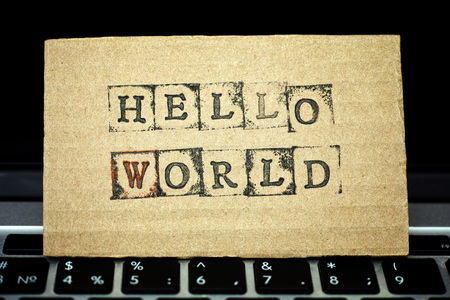 alphabet keyboard: ?ardboard with words Hello World maked by black alphabet stamps standing on laptop keyboard.