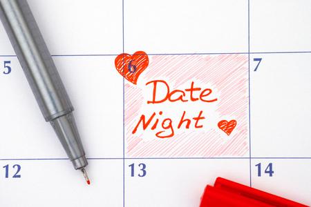 Recordatorio noche de la fecha en el calendario con la pluma roja Foto de archivo