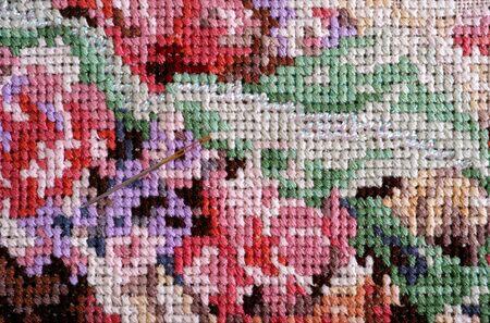 cross stitch: Multicolor cross stitch with needle. Close up.