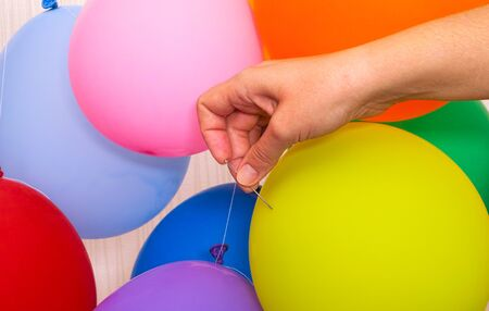 Woman hand with needle ready to pop a yellow balloon. There are some balloons around.