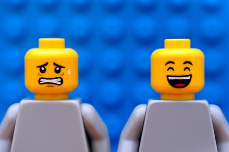Tambov, Rusland - 24 juli 2016 Twee Lego figuurtjes - een bang en een gelukkig. Blauwe achtergrond. Studio-opname.