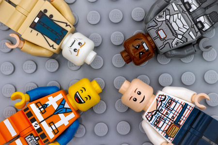Tambov, Russian Federation - July 06, 2016 Four Lego minifigures with with different color heads and different emotions on faces on Lego gray baseplate background. Studio shot.