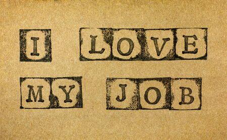 Words I Love My Job make by black alphabet stamps on cardboard. Stock Photo