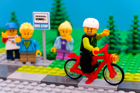 mini bike: Tambov, Russian Federation - July 30, 2016 Lego boy riding bicycle waving to his friends, who standing at bus stop. Studio shot. Editorial