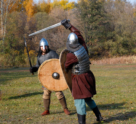 panoply: Tambov, Russian Federation - October 12, 2014 Two warriors in old Russian armors reconstructed medieval fight with swords and shields on battlefield.