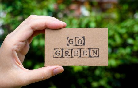 go green background: Woman hand holding cardboard card with words Go Green made by black alphabet stamps opposite green floral background. Stock Photo