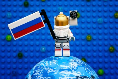 astronautics: Tambov, Russian Federation - July 06, 2016 Lego spaceman minifigure with Russian flag stay on planet against Lego blue baseplate with stars. Studio shot.