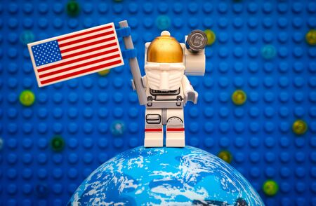 astronautics: Tambov, Russian Federation - July 06, 2016 Lego spaceman minifigure with American flag stay on planet against Lego blue baseplate with stars. Studio shot. Editorial