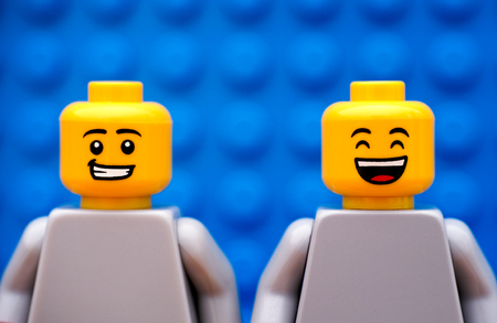 yellow lego block: Tambov, Russian Federation - July 24, 2016 Two Lego minifigures - one with smirk and one happy. Blue background. Studio shot.
