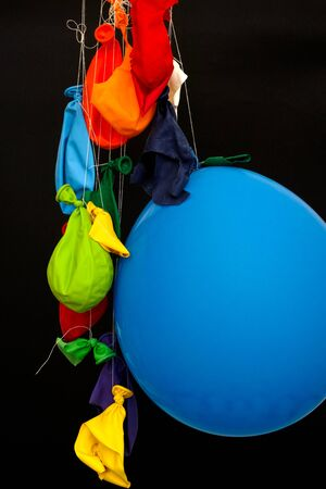 deflated: End of the party. Some burst, deflated balloons and one inflated balloon hanging on threads. Black background.
