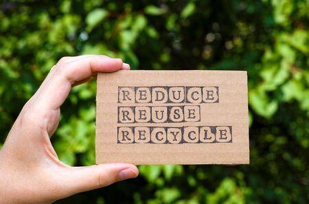 recycle reduce reuse: Mano de la mujer que sostiene la tarjeta de cartón con las palabras reduce la reutilización recicla hecha por sellos alfabeto negro opuestos fondo floral verde.