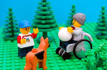 Tambov, Russian Federation - July 30, 2016 Lego boy in wheelchair playing ball with friend and dog in park. Studio shot. Editorial