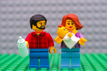 Tambov, Russian Federation - September 21, 2016 Lego family minifigures - father, mother and baby. Studio shot.