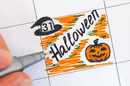 person writing: Person hand with pen writing reminder Halloween in calendar.