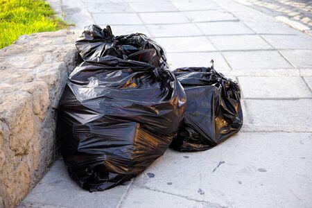 black plastic garbage bag: Full black plastic trash bags in the street Stock Photo
