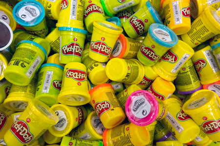 playdoh: Paphos, Cyprus - October 18, 2016 Heap of Play-Doh containers with difrent color  modeling compound. Play-Doh is manufactured by Hasbro.