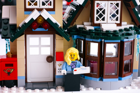 Tambov, Russian Federation - March 10, 2015 Lego winter post office. Lego woman minifigure with letter stand near post office. Studio shot.