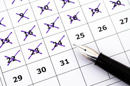 Fountain pen lying on calendar with marking days.