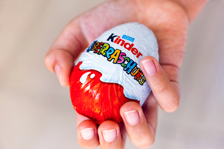 Paphos, Cyprus - November 21, 2016 Child hand with Kinder Surprise egg. Word Surprise written in German. Manufactured by Italian company Ferrero.