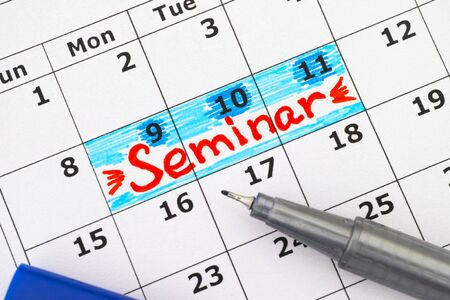 blue pen: Reminder Seminar in calendar with blue pen. Focus on calendar. Stock Photo