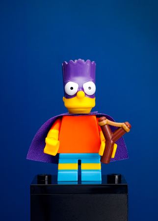 Tambov, Russian Federation - June 08, 2015 Lego Bart Simpson minifigure as a Bartman with slingshot on blue background. Studio shot.