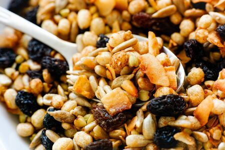 sultanas: Gluten free blend of toasted buckwheat and crisped rice with mixed seeds, dried fruit and coconut in plate with spoon