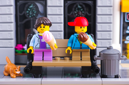 Tambov, Russian Federation - January 21, 2017 Lego girl and boy with ice creams seating on the bench in Lego street. Red cat is near bench. Studio shot.