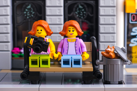 Tambov, Russian Federation - January 21, 2017 Two Lego girls seating on the bench in Lego street. One of girl holding camera. Cat looks out of garbage can. Studio shot. Editorial