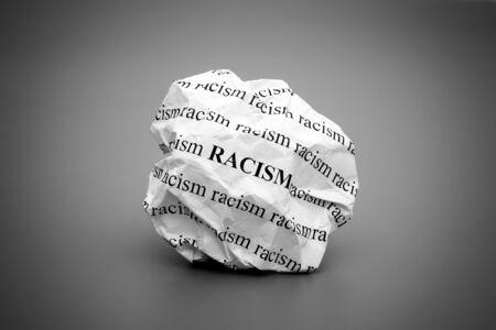 Verfrommeld papier bal met woorden racisme op grijze achtergrond. Zwart en wit.
