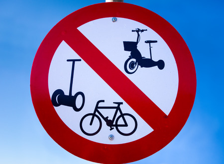 motorizado: Prohibition road sign - No bicycles, no segway and other motorized vehicles - against blue sky. Foto de archivo