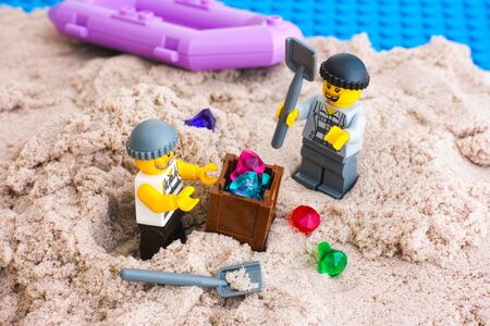 Tambov, Russian Federation - January 24, 2017 Two Lego robbers digging out box of gems from sand on the island. Studio shot.