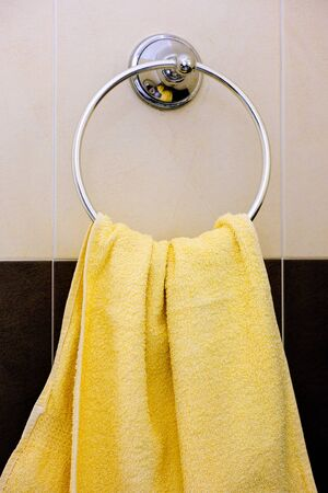 Yellow towel hanging on towel ring in bathroom