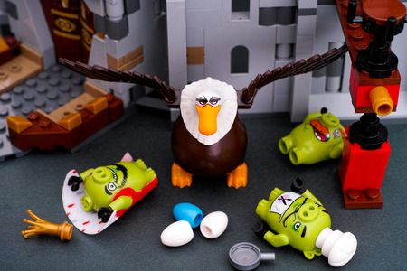 Tambov, Russian Federation - July 20, 2016 Lego Angry Birds. Three Bad Piggies defeated by Mighty Eagle near King Pigs Castle. Studio shot.
