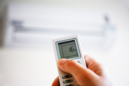 Person hand using remote control of air conditioner.