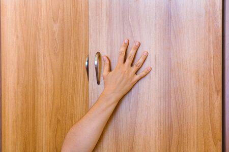 closet door: Woman hand protruding from wardrobe door. Person inside of wardrobe. Stock Photo