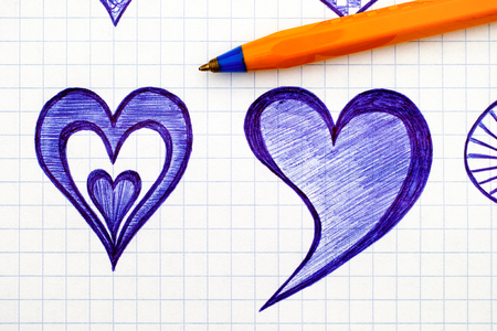 Close-up of hand drawn hearts on the sheet of checkered paper with ballpoint pen. Doodle style.