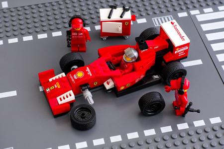 Tambov, Russian Federation - June 23, 2015 Lego team crew members fixing wheel of Lego Speed Champions Ferrari F14 T race car. Studio shot. Editorial