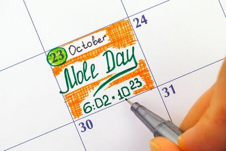 カレンダーでアラームほくろ日を書くペンで女の指。モルの日は、6-2 と 6-14 の間、化学者の間で 10 月 23 日祝われる非公式な休日です。