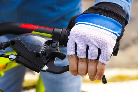 Child hand with glove on handlebars with brake lever. Close-up. Stock Photo