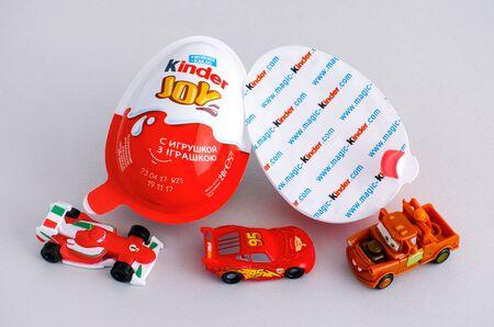 Tambov, Russian Federation - June 01, 2017 Kinder Joy eggs with three Kinder Ð¡ars toys on gray background. Kinder Joy manufactured by Italian company Ferrero. Studio shot. Editorial